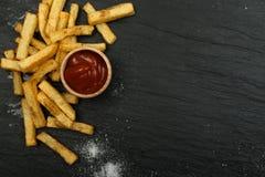 Pommes frites avec le ketchup sur le fond foncé photographie stock libre de droits