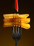 Pommes frites avec le ketchup sur la fourchette originale sur un fond noir images libres de droits