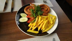 Pommes frites cuites à la friteuse de pommes de terre avec des saucisses Images libres de droits