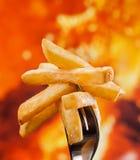 Pommes frites délicieuses coincées sur la fourchette - fond du feu photographie stock libre de droits
