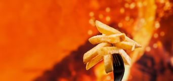 Pommes frites délicieuses sur une fourchette - fond du feu avec l'espace de copie images stock