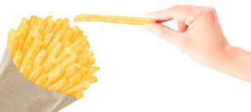 Pommes frites dans le sac de papier avec la main photo libre de droits