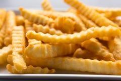 Pommes frites dans un plat blanc sur une table en bois Photo libre de droits