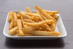 Pommes frites dans un plat blanc sur une table en bois Photographie stock