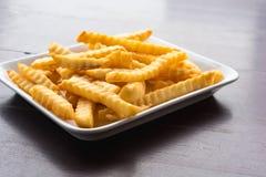 Pommes frites dans un plat blanc sur une table en bois Photos stock