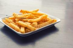 Pommes frites dans un plat blanc sur une table en bois Images libres de droits