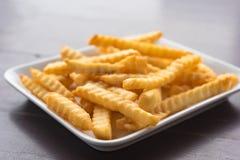 Pommes frites dans un plat blanc sur une table en bois Images stock