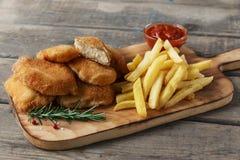 Pommes frites de pépites de poulet sur le conseil avec de la sauce rouge Photographie stock libre de droits