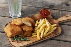Pommes frites de pépites de poulet sur le conseil avec de la sauce rouge photographie stock