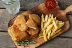 Pommes frites de pépites de poulet sur le conseil avec de la sauce rouge Images stock