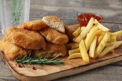 Pommes frites de pépites de poulet sur le conseil avec de la sauce rouge Photo libre de droits