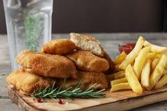 Pommes frites de pépites de poulet sur le conseil avec de la sauce rouge image libre de droits