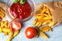 Pommes frites, pommes de terre frites avec le ketchup et tomates sur le fond du granit gris-bleu photos libres de droits
