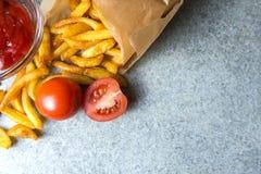 Pommes frites, pommes de terre frites avec le ketchup et tomates sur le fond du granit gris-bleu images stock