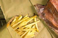 Pommes frites et saumons frits frais sur le fond en bois Un fond texturisé Copiez l'endroit de pâte photo stock