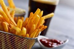 Pommes frites i en metallkorg och en sodavatten royaltyfri bild