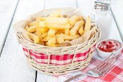 Pommes frites i en vide- korg på den vita tabellen - stång- eller snabbmatmeny fotografering för bildbyråer