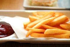 Pommes frites i en vit maträtt på tabellen Arkivbilder