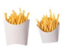 Pommes frites i ett pappers- omslag på vit bakgrund Arkivbild