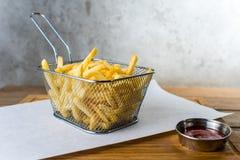 Pommes frites i järnraster och sås arkivfoto