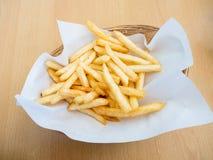 Pommes frites i korg på träbakgrund Royaltyfria Foton