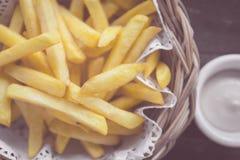 Pommes-Frites im hölzernen Korb mit Soße, selektiver Fokus poin Lizenzfreie Stockbilder