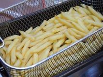 Pommes-Frites im heißen Fett in einer Fritteuse stockfotos