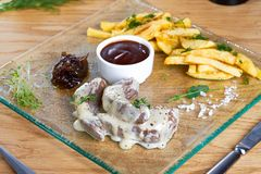 Pommes frites med det grillade kalvköttet tjänade som med sås på den glass plattan Läcker potatis med kött i sås på trätabellen royaltyfri foto