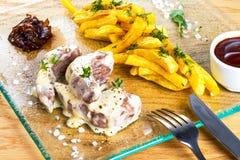 Pommes frites med det grillade kalvköttet tjänade som med sås på exponeringsglasfyrkantplattan med gaffeln och kniven Smaklig ste fotografering för bildbyråer