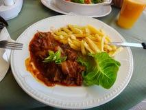 Pommes frites med kött Arkivfoton