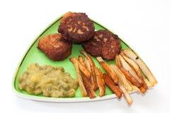 Pommes frites med köttbullar och ärtor på en platta Royaltyfria Bilder