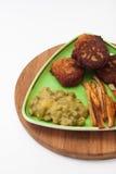 Pommes frites med köttbullar och ärtor på en platta och ett träbräde Royaltyfria Bilder