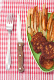 Pommes frites med köttbullar och ärtor på en platta- och köktabl Arkivfoto