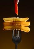 Pommes-Frites mit Ketschup auf der ursprünglichen Gabel auf einem schwarzen Hintergrund Stockfotos