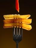 Pommes-Frites mit Ketschup auf der ursprünglichen Gabel auf einem schwarzen Hintergrund Lizenzfreie Stockbilder