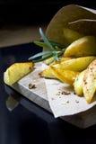 Pommes-Frites mit Kräutern und Gewürzen in aufbereiteter Kraftpapiertasche Lizenzfreie Stockfotografie