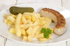 Pommes frites och grillad korv Arkivfoto