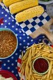 Pommes frites och havremajskolv på trätabellen med 4th det juli temat Royaltyfri Bild