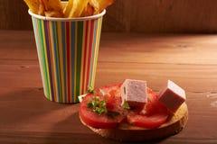 Pommes frites och ostsmörgås och tomat fotografering för bildbyråer