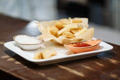 Pommes frites och potatisbollar med tomaten och vit sås i en vit platta på en trätabell royaltyfria foton