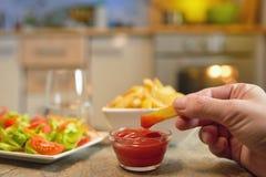 Pommes frites och sallad på tabellen royaltyfria bilder