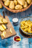 Pommes frites som göras från potatisar på blåtttabellen Royaltyfria Bilder