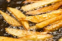 Pommes frites som stekas i en panna arkivbild