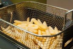 Pommes frites som stekas i olje- guld- patato fotografering för bildbyråer