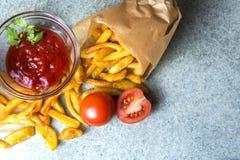 Pommes frites, stekte potatisar med ketchup och tomater på bakgrunden av grå färg-blått granit arkivbild