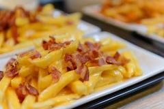 Pommes-Frites und Käse mit Speck auf die Oberseite in der weißen Schüssel Lizenzfreie Stockfotos