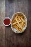 Pommes-Frites und Tomatensauce auf Holztisch Lizenzfreie Stockfotografie