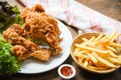 Pommes-Friteskorbketschup auf h?lzernem Speisetischhintergrund und gebratenen dem Huhn knusperig und Salatkopfsalat lizenzfreies stockbild