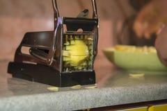 Pommes-Fritesschneidemaschine, manuelle Kartoffelschneiderschneidmaschine Der Prozess des Kochens von Pommes-Frites lizenzfreies stockfoto