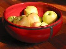 Pommes jaunes dans une cuvette rouge Images libres de droits